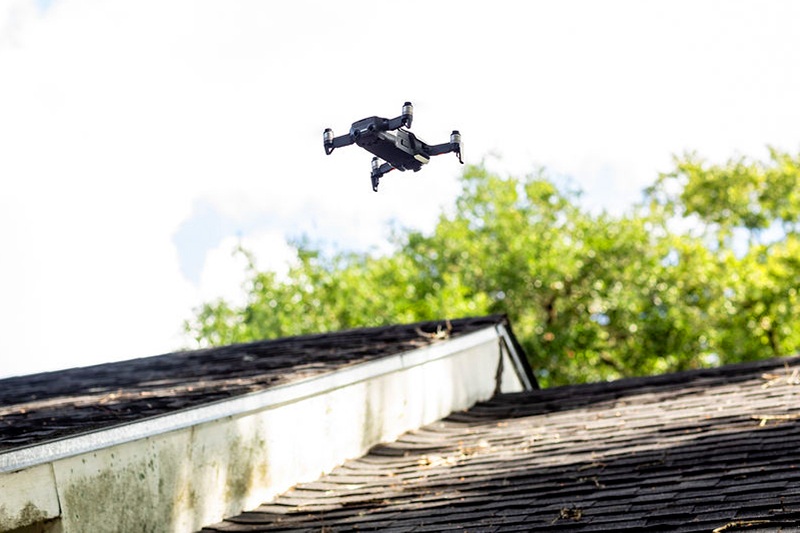 Aerial drone flying over the roof of a home inspection service