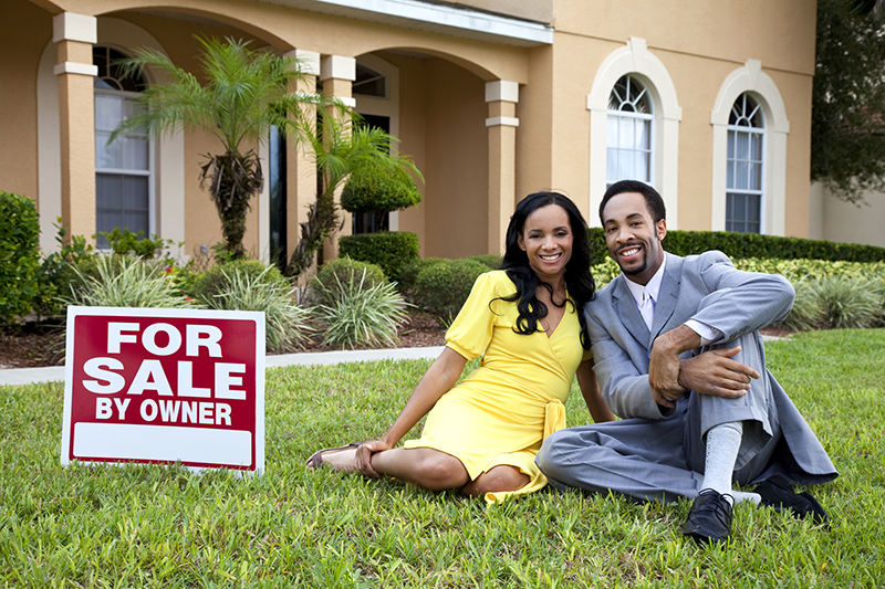 A couple sitting in the grass next to a For Sale By Owner sign in front of their Florida home