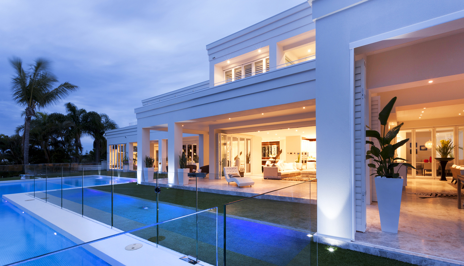 Beautiful white villa with warm ilumination and a fancy swimming pool as seen during a home inspection
